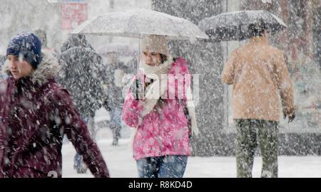 Belgrade, Serbia - December 15, 2018: One teenage girl walking under umbrella in heavy snowfall in city street crowd - Stock Photo