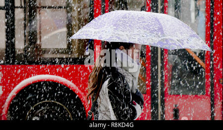Belgrade, Serbia - December 15, 2018: One young woman walking under umbrella in heavy snowfall in city street in front of the red bus - Stock Photo