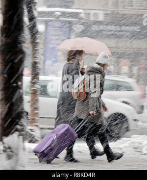 Belgrade, Serbia - December 15, 2018: Two teenage girls walking under umbrella in heavy snowfall in city street and one is rolling a wheeled suitcase  - Stock Photo