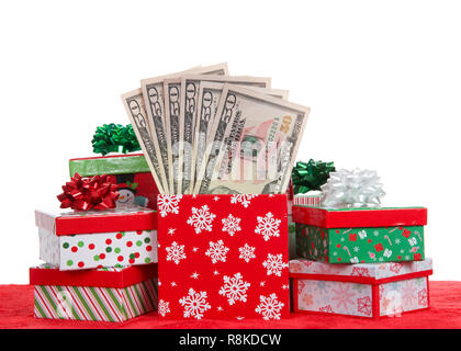 Christmas presents stacked on a red velvet surface. Box stuffed with 50 dollar bills. Representing cost of the holidays and gifts of money. - Stock Photo