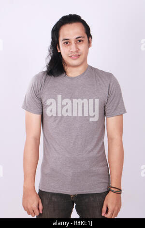 Photo image of an Asian Model smiling and showing blank grey T-Shirt, front view, shirt template - Stock Photo