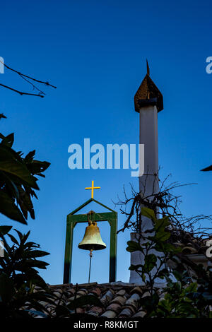 Greek Orthodox monastery roof details, brass bell on stand, golden cross and tall chimney over red tiled roof in clear blue sky spring day - Stock Photo