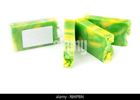 Handmade green and yellow artisan jojoba soap bars on white background - Stock Photo
