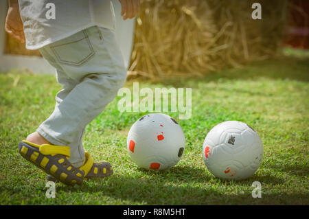Happy little cute boy playing soccer outside home or school in summer day. Preschool kid play football in green grass lawn. Child with casual shoes pl - Stock Photo