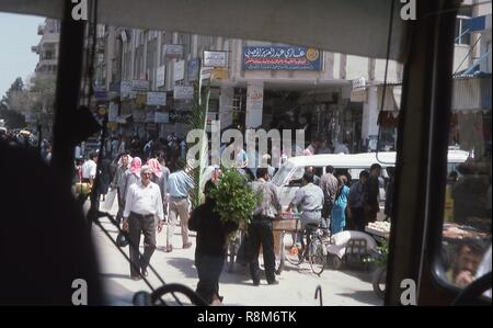 View of a busy street as seen through the windshield of a tour bus traveling through Damascus, Syria, June, 1994. Men and women crowd the sidewalk stalls and store entrances. A large blue advertising sign at top center translates to: 'Doctor Ghazi Abdul Aziz al-Hasni, obstetrician, gynecologist and fertility treatment, diagnosis, ultrasound, echograph'. () - Stock Photo