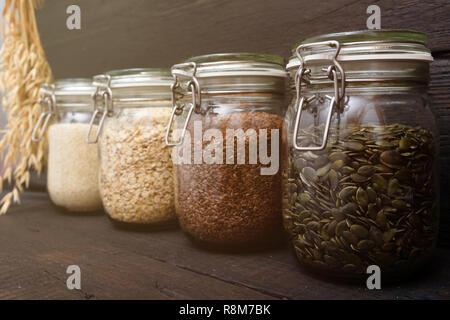 Various seeds in storage jars in pantry, dark wooden background. Smart kitchen organization - Stock Photo
