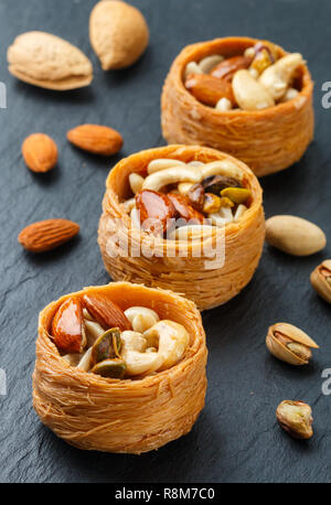 Traditional middle Eastern sweets 'bird's nest' in honey syrup with nut filling - almonds, cashews, pistachios. Baklava close-up. Delicious dessert. S