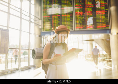 theme travel and transportation. Beautiful young caucasian woman in dress and backpack standing inside train station terminal looking at electronic sc - Stock Photo