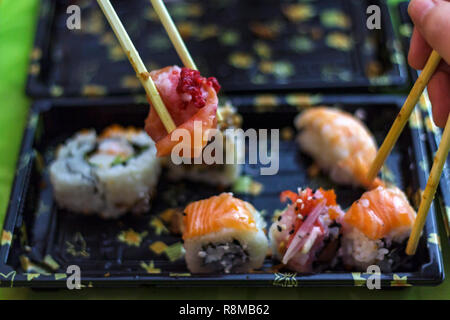 Eat sushi with chopsticks at the same time - Stock Photo