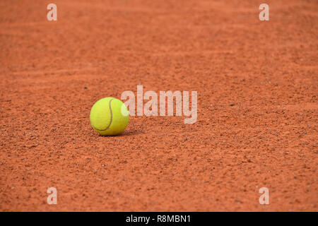 Close up one yellow felt tennis ball on red brown clay ground court, low angle view - Stock Photo