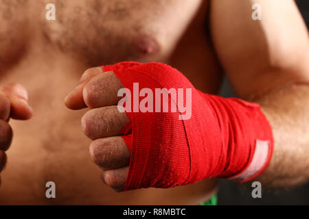 Close up boxer man with red wrist wraps on hands ready to fight, low angle view - Stock Photo