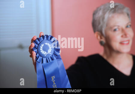 Mature woman showing her blue ribbon prize, USA - Stock Photo
