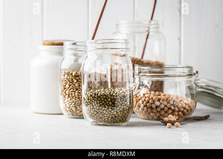 Various legumes: beans, chickpeas, buckwheat, lentils in glass jars on a white background. Healthy vegetarian food, vegetable protein, plant based die - Stock Photo