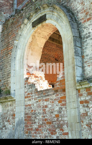Arch, partially laid bricks in the wall of old destroyed Christian church - Stock Photo