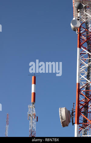Several kind of communication antennas against deep blue sky - Stock Photo