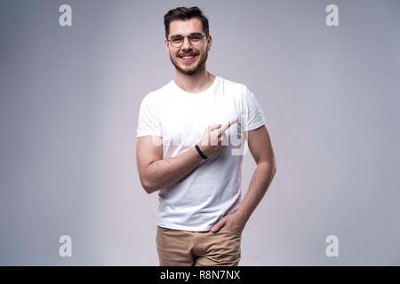 smiling young casual man presenting something on gray background. - Stock Photo
