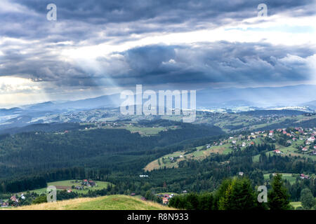 Sunbeams through clouds over Silesian Beskids mountains. View on Koniakow village from the peak of Ochodzita Mountain. Poland, Europe - Stock Photo