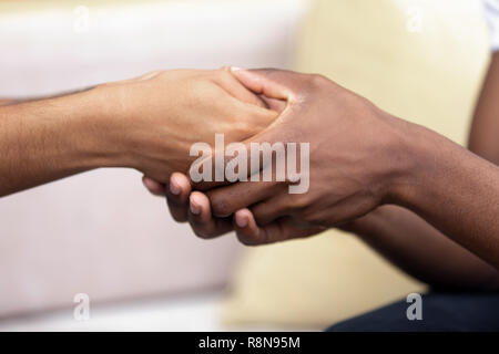 African American man holding hands of beloved woman close up - Stock Photo