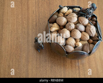 Silver bowl with two silver squirrel figurines  photographed on a wooden table from above. Bowl contained unshelled mixed nuts. - Stock Photo