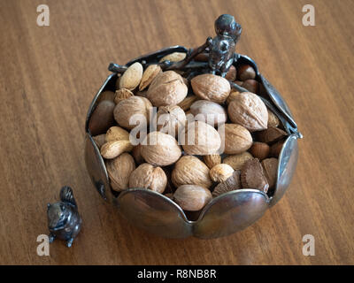 High angle view of a silver bowl with squirrel figurines. Mixed nuts with shells are in the bowl. - Stock Photo