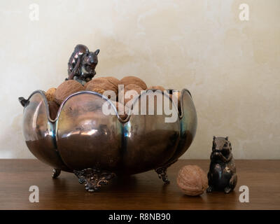 Tarnished decorative silver bow with squirrel figurines and mixed nuts in the shell. Photographed at eye level. Copy space. - Stock Photo