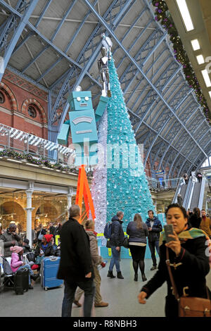Tiffany & Co Christmas tree and robot & woman taking selfie in shopping mall area at St Pancras International Railway Station London UK  KATHY DEWITT - Stock Photo