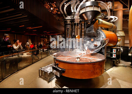 People watch freshly roasted coffee beans pour from a large Probat roaster located inside Starbucks Reserve Roastery New York - Stock Photo