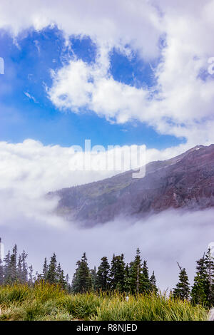 clouds and mountain top with meadow and trees below - Stock Photo