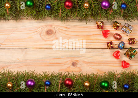 Christmas frame made of fir branches decorated with balls on a light wooden background - Stock Photo