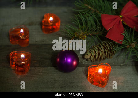 Christmas composition of fir branches decorated bows and balls with burning candles on a wooden background - Stock Photo