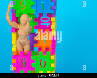 action figure standing in colorful plastic number and make a headache acting on blue background. Concept of education. copy space for text and content - Stock Photo