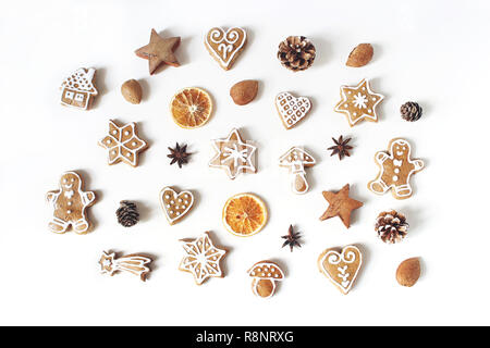 Decorative Christmas food pattern. Winter composition of gingerbread cookies, anise stars, pine cones and dry orange fruit slices isolated on white table background. Flat lay, top view. - Stock Photo