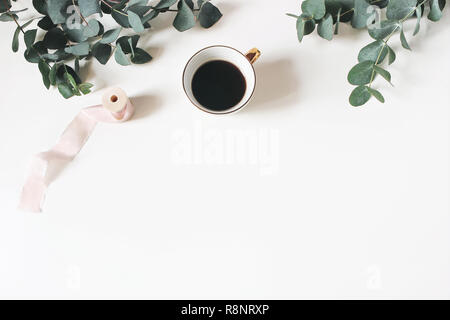 Floral composition made of green eucalyptus leaves and branches on white wooden background with cup of coffee and silk ribbon. Feminine office desk, styled stock image. Flat lay, top view. - Stock Photo