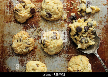 Chocolate chips cookies on baking sheet with raw dough on vintage spoon. - Stock Photo