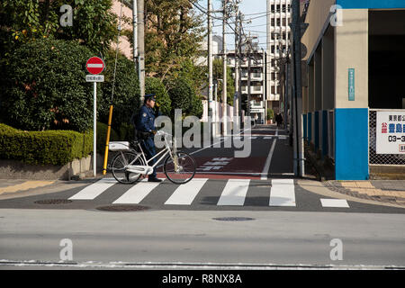 A Japanese policeman with bicycle walking in the Ikebukuro area in Tokyo - Stock Photo
