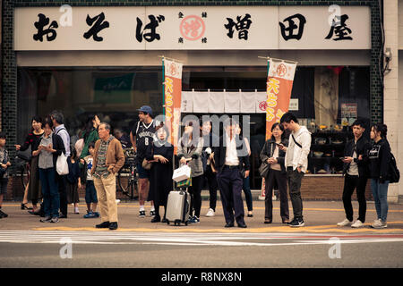 Japanese members of the public waiting to cross the road in the Shinjuku area of Tokyo - Stock Photo