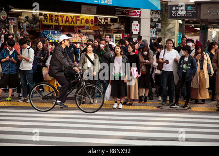 Japanese pedestrians waiting to cross a road in the Shibuya area of Tokyo. - Stock Photo