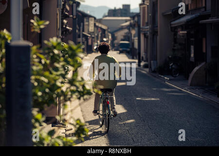 An elderly Japanese lady cycles down an elegant traditional street in Kyoto, Japan. - Stock Photo