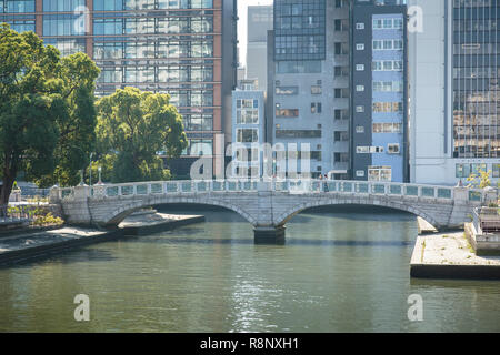 An elderly couple walking over the old Nakanoshima Koen Barazono Bridge in Osaka, Japan