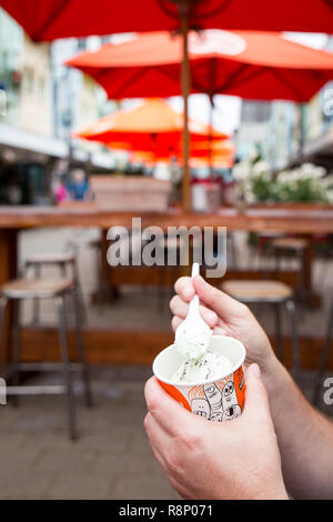 A tourist enjoys a tub of gelato in New Regent Street, Christchurch, New Zealand - Stock Photo