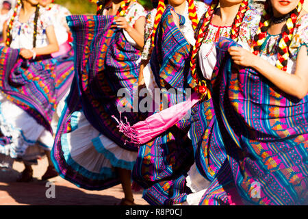 dance crew of female dancers wearing colorful traditional dresses dance waving her long skirts - Stock Photo