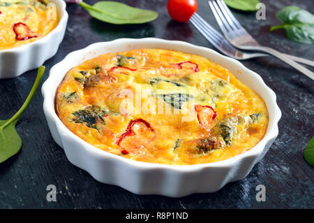 Frittata with fresh vegetables and spinach. Italian omelet in ceramic forms on a black background. - Stock Photo
