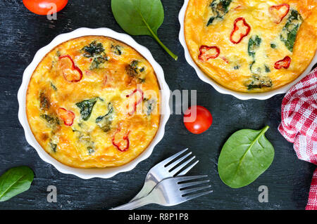 Frittata with fresh vegetables and spinach. Italian omelet in ceramic forms on a black background. Top view. - Stock Photo
