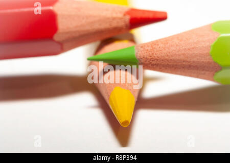 Macro of red yellow green color pencils, on top of each other on white paper. - Stock Photo