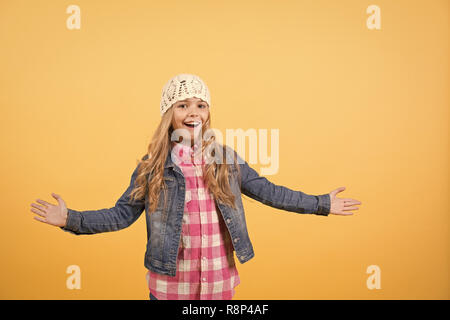 Girl with long blond hair in jeans jacket, hat, plaid shirt smile with open hands on orange background. Happy child and childhood. Fashion, beauty, style, look concept. - Stock Photo