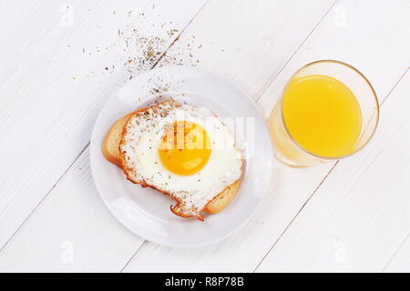 Scrambled eggs orange juice on a white wooden table - Stock Photo