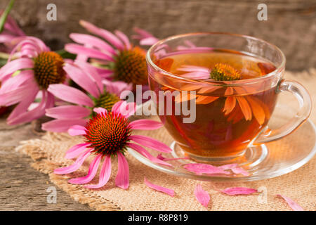 Cup of echinacea tea on old wooden table - Stock Photo