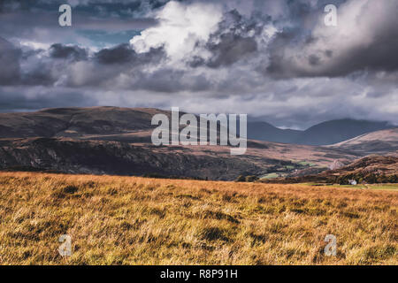 Beautiful sky with clouds rolling over scenic mountain valley and light painting on hill slopes in Lake District, Cumbria, UK.Idyllic landscape scene. - Stock Photo