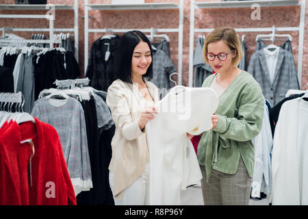 Sales consultant helping chooses clothes for the customer in the store. Shopping with stylist concept. Female shop assistant and young woman in the fashion boutique - Stock Photo