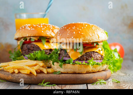 Two fresh homemade burgers with fried potatoes and orange juice on a wooden table - Stock Photo